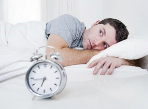 Guy lying in bed with alarm clock