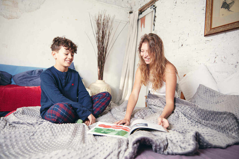 happy woman and teenage boy reading under weighted blanket