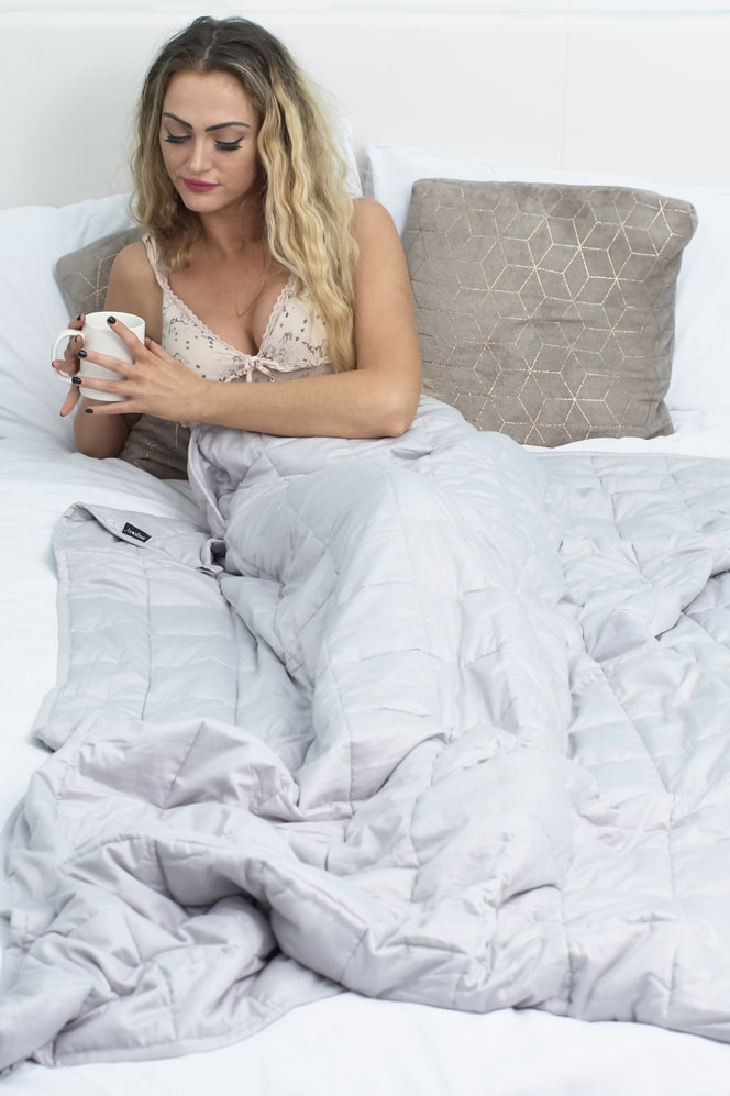 single weighted blankets over female model on bed