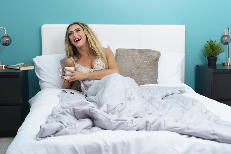 lady lying in bed under double weighted blanket  holding mug coffee
