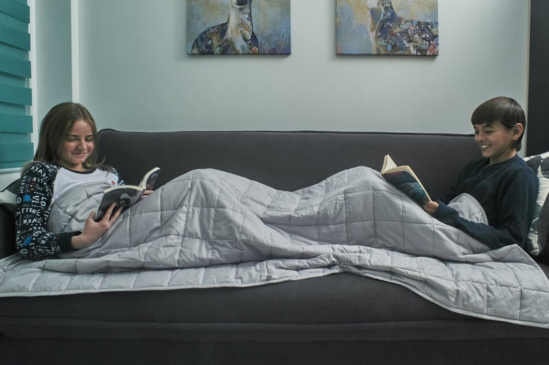 two young teens lying on couch covered by weighted blanket for kids