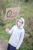 Child wearing a grey hoodie sweatshirt with born to explore printed slogan holding a Buy Organic Banner
