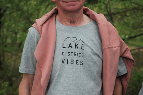 A man wearing a unisex organic cotton grey t shirt with a Lake District Vibes print