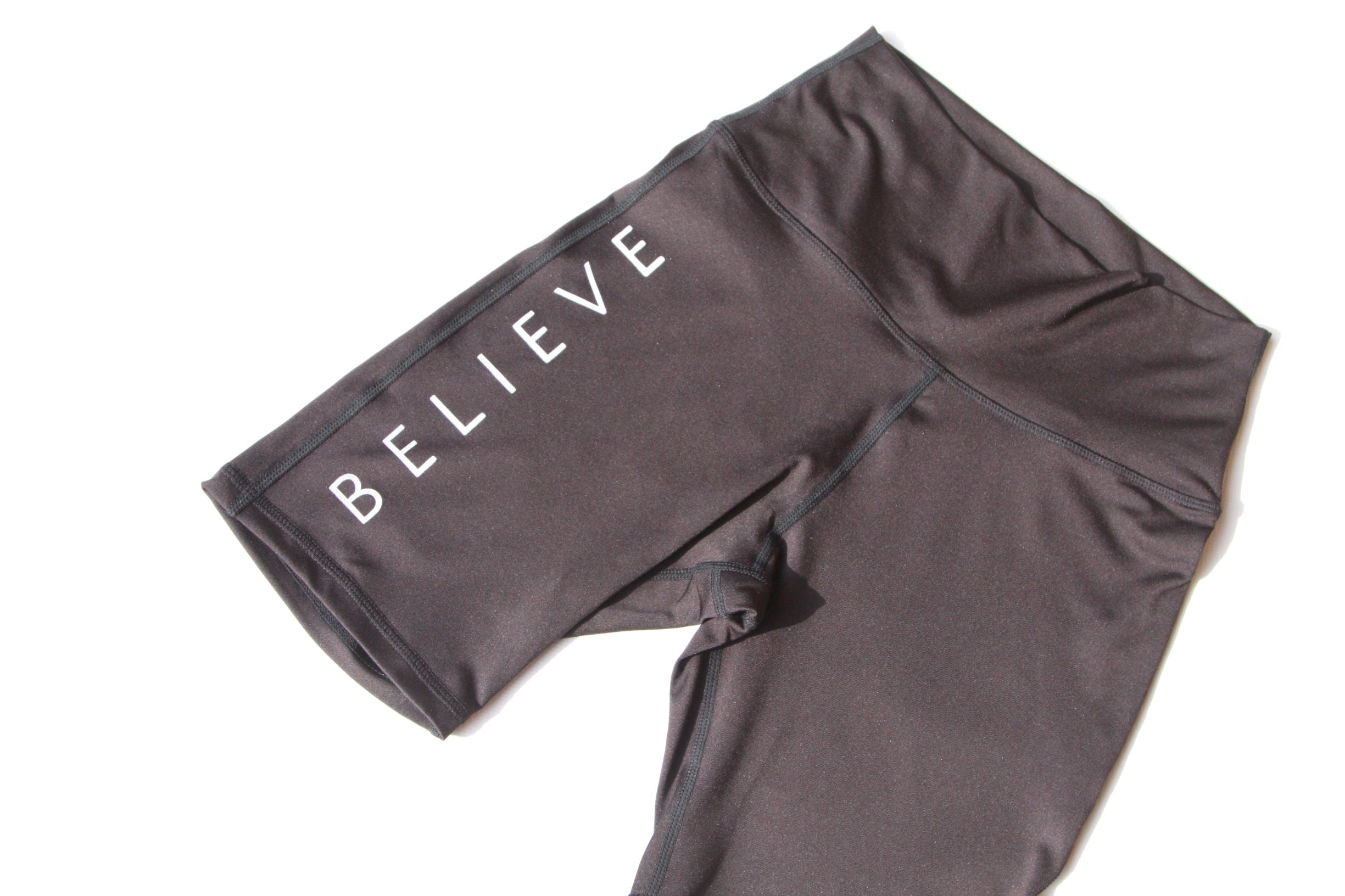 Black high waisted sports shorts with the word Believe printed on one leg in white ink