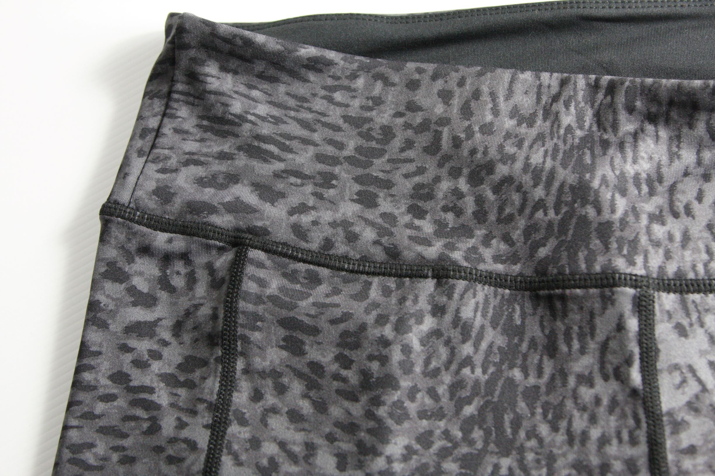 A close up of the thick waistabnd and seem detail of leopard print sports leggings in grey and black