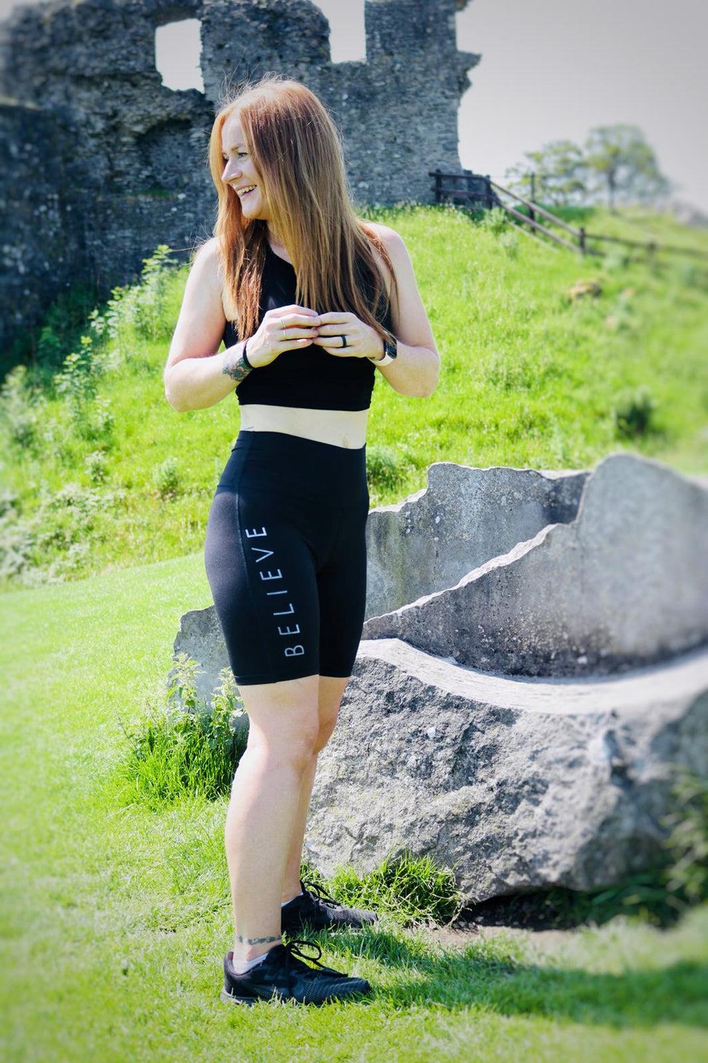 Lynsey Goodyear wearing black high waisted sports shorts featuring the word Believe in white ink