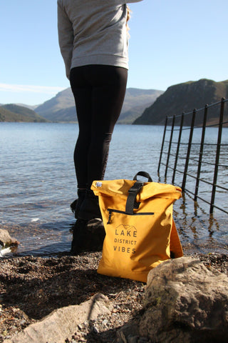 Mustard rucksakc with black Lake District Vibes design next to a lady admiring a view across Ennerdale Lake
