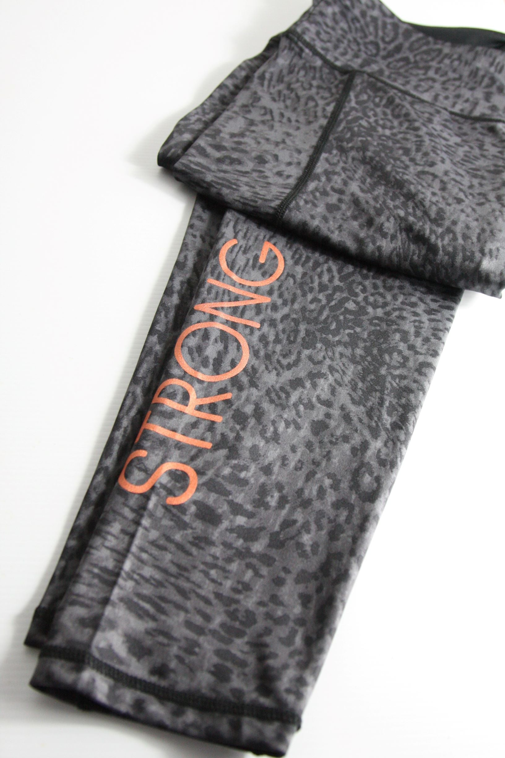 Leopard print sports leggings in grey and black with the word STRONG printed in copper ink
