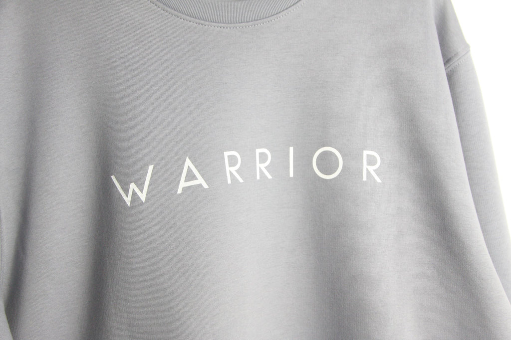 Close up of lilac grey classic sweatshirt featuring WARRIOR screenprinted in white ink