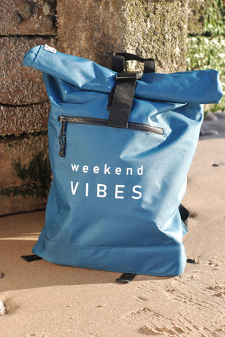petrol blue rucksack with front zip detail and white weekend vibes design