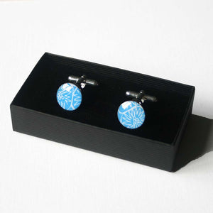 A pair of blue cufflinks in a branded gift box handmade in Cambridge, UK, from silver, card and resin