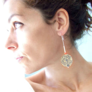 A women wearing a pair of large drop earrings handmade from silver, paper and resin by Dittany Rose