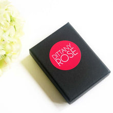 A black jewellery box branded with Dittany Rose pink circle logo