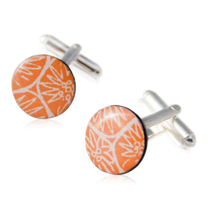 A pair of orange cufflinks handmade in Cambridge, UK, from silver, card and resin