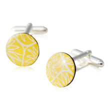 A pair of yellow cufflinks handmade in Cambridge, UK, from silver, card and resin