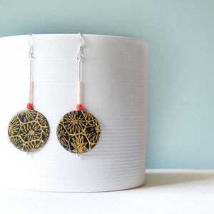 A pair of large black and gold drop earrings handmade from silver, paper and resin by Dittany Rose