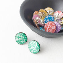 A green pair of large stud earrings handmade from silver, paper and resin by Dittany Rose