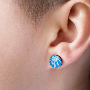 A close up of a blue stud earring being worn, handmade by Dittany Rose in Cambridge, UK from paper, sterling silver and resin