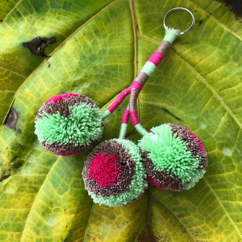 Keychain with 3 pompoms handmade in Colombia, multicolor, green,pink and brown . It can be used to decorate any spot in tour house, planters,walls or as a handbag accessory or key ring.