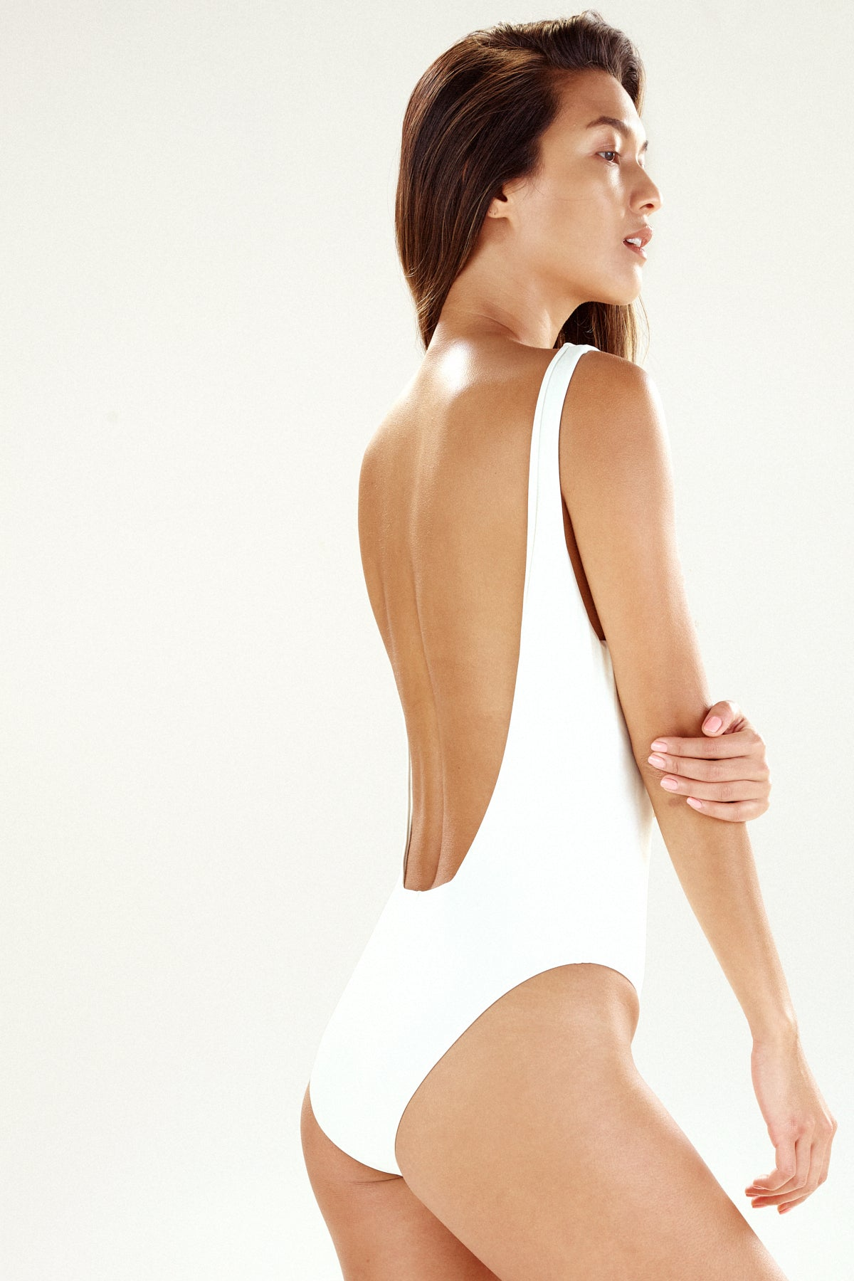 Side/back view of the Lisbon one-piece by Ookioh in cream