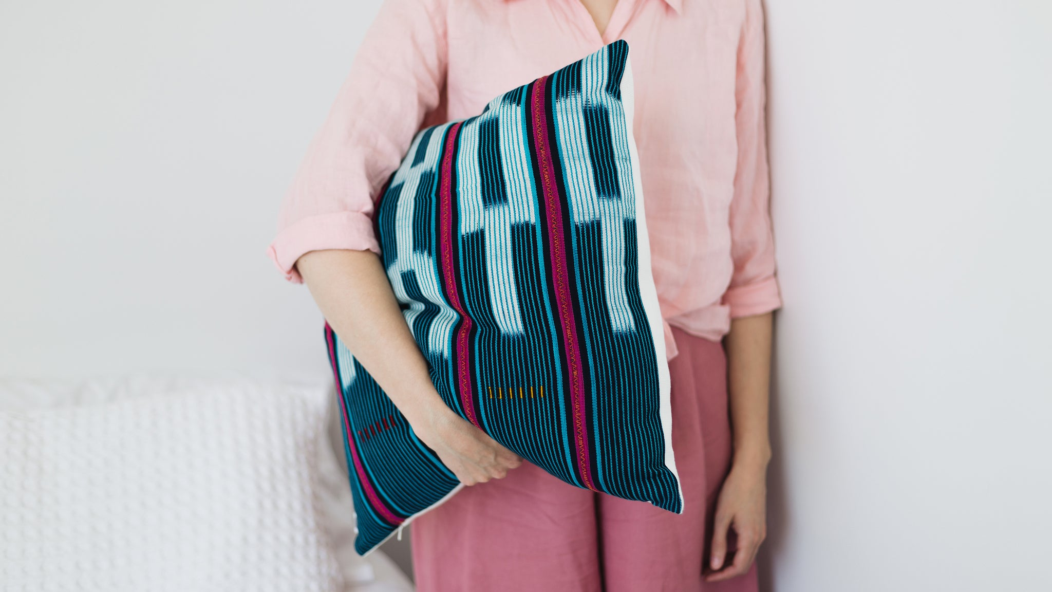 Ethical hand dyed, hand woven artisan crafted blue turquoise and pink baoule cushion made by former refugees building new lives in New Zealand