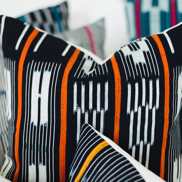 Ethical navy orange stripe baoule cushion made by former refugees using traditionally made artisan-crafted fabric. Contemporary global interior style with soul
