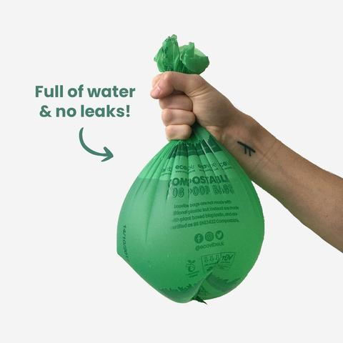 plastic-free poop bag full of water being held by a hand demonstrating how strong it is