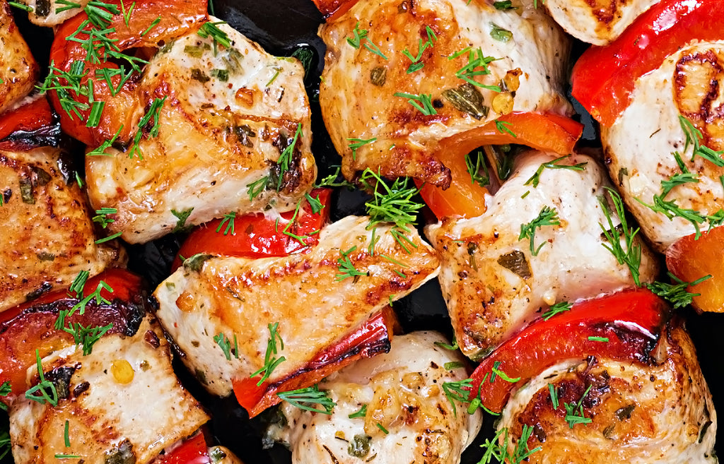Image of grilled chicken with red pepper pieces on skewers
