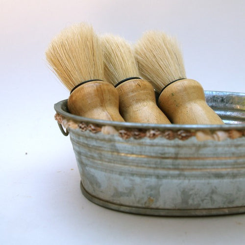 old fashioned shaving brushes in tin
