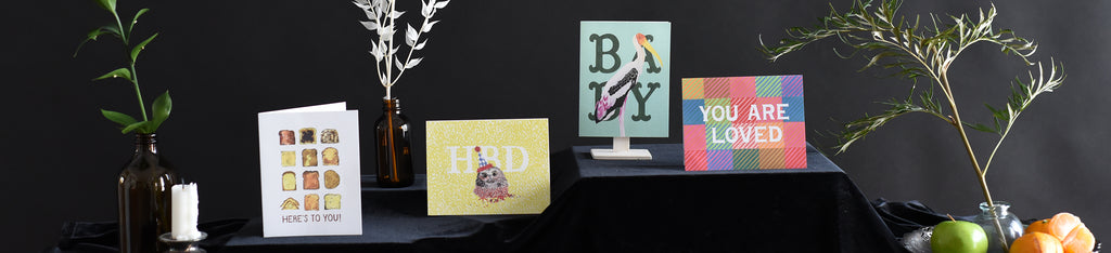 Four Front Paper greeting cards arranged on a background of black velvet