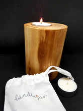 wooden tealight holder with lit tealight next to a canvas bag of scented tealights