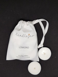 2 soy wax tealights next to a white canvas bag with Candle Jar on it. Lomond is the scent