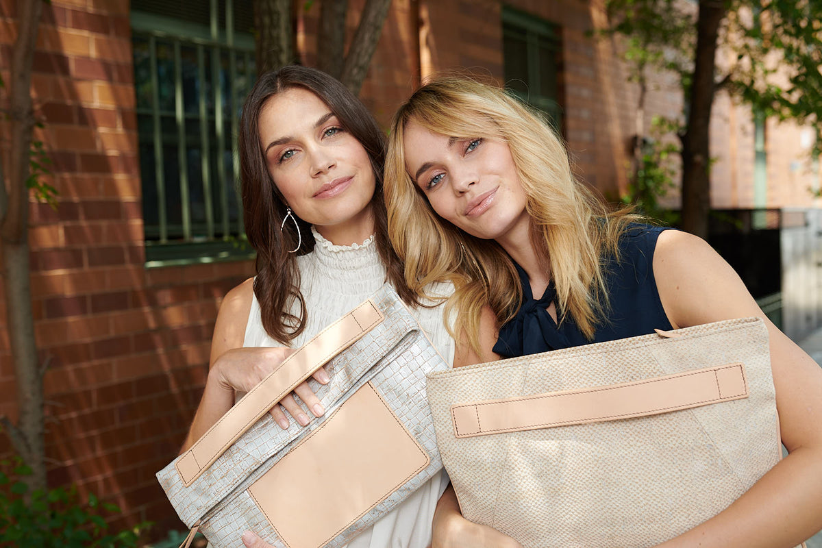 A brunette and a blond outside a New York brick building holding luxe designer clutches made of cork fabric