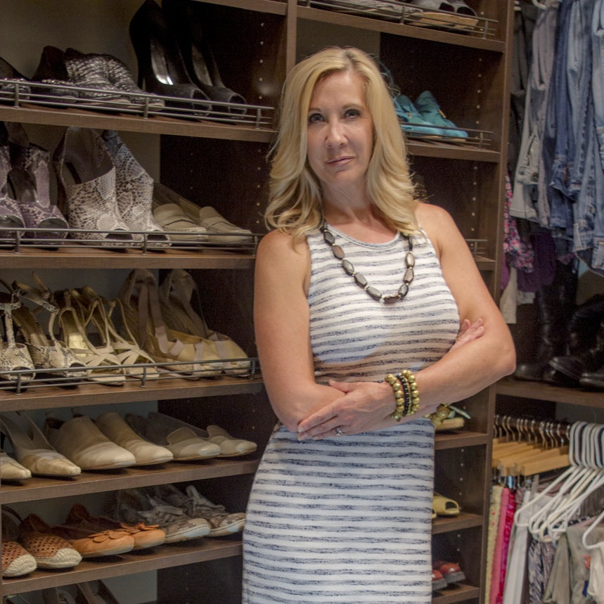 Santa Barbara California Personal stylist and cork accessories designer, Paula Parisotto, standing inside her closet, in front of hundreds of shoes, smiling.