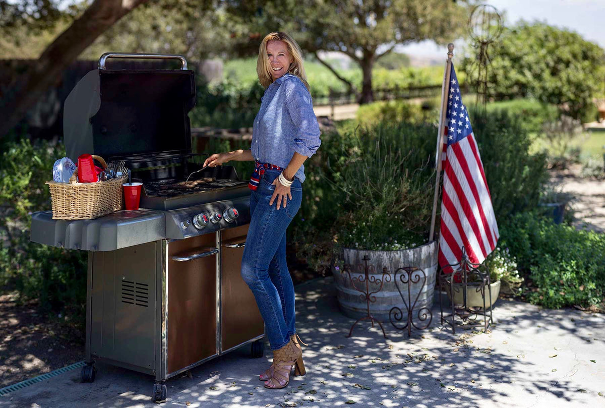 Santa Barbara California accessories designer and personal stylist, Paula Parisotto, wears jeans, a blue and white gingham button up, and tan heels while BBQing for Independence Day