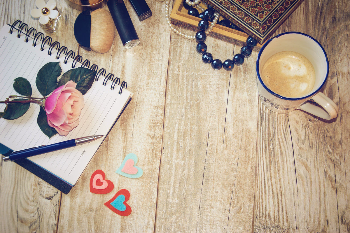 View of a wooden table from above with a cup of coffee, jewelry, pen and journal with tips for accessorizing your look