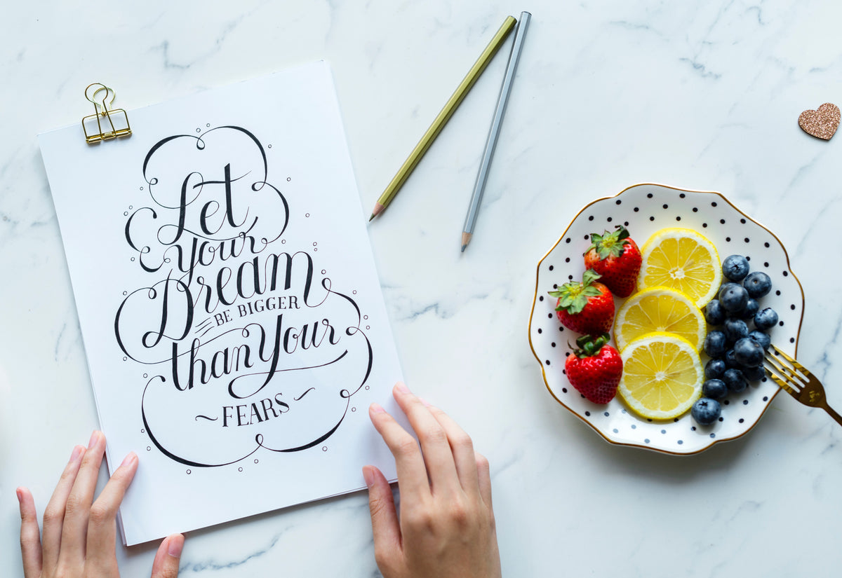 "Arial view of a marble table where a woman has a journal entitled, ""Let your dreams be bigger than your fears"", a plate of fresh fruit and a pen."