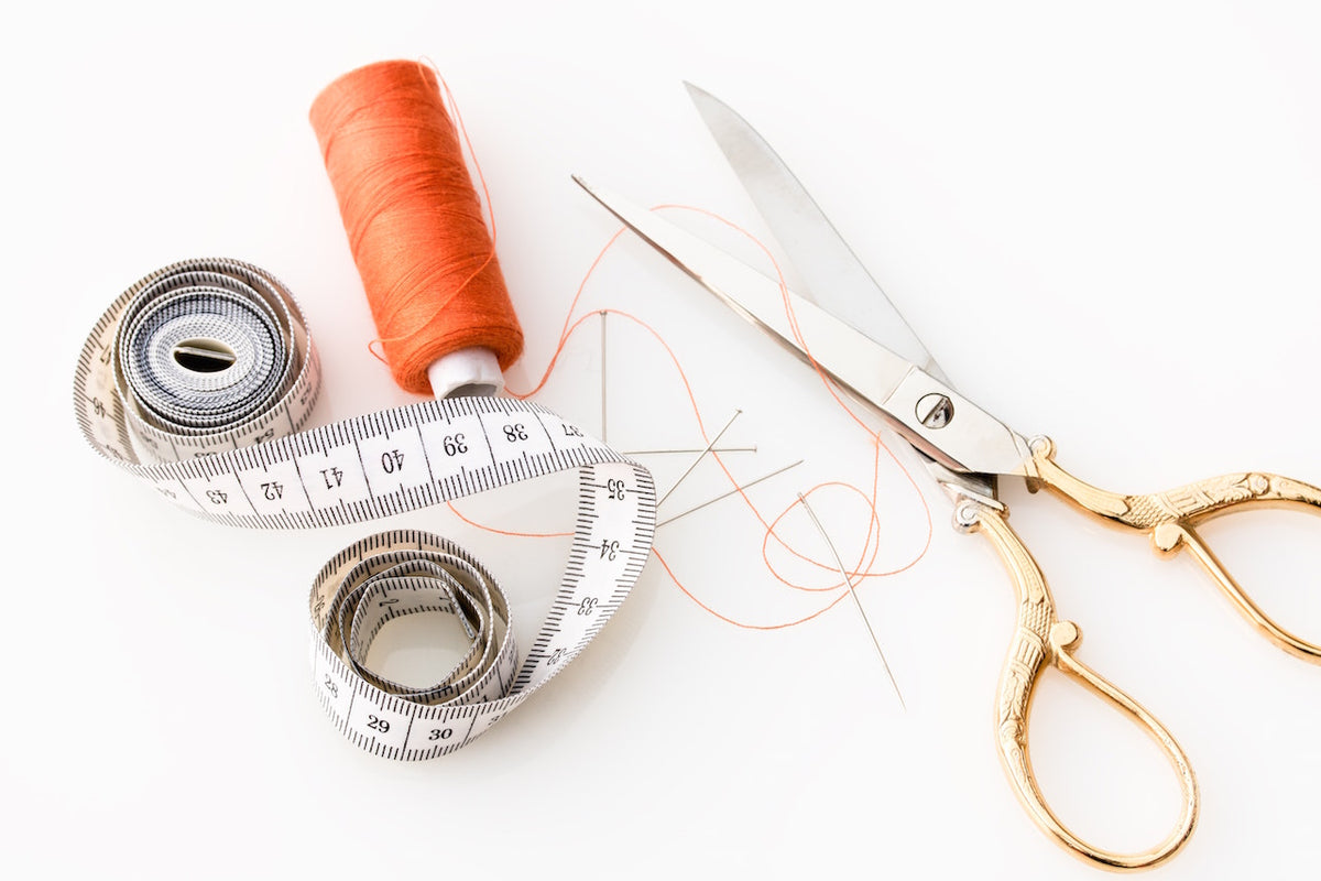 A tape measure, thread and scissors lay on a table ready to sew cork purses.