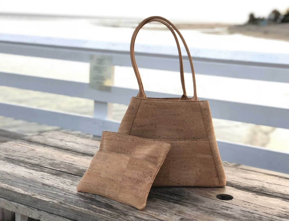 Two unique cork bags, a wristlet and shoulder bag or tote purse, made in the of cork fabric sit on an old wood picnic table on a beach pier.