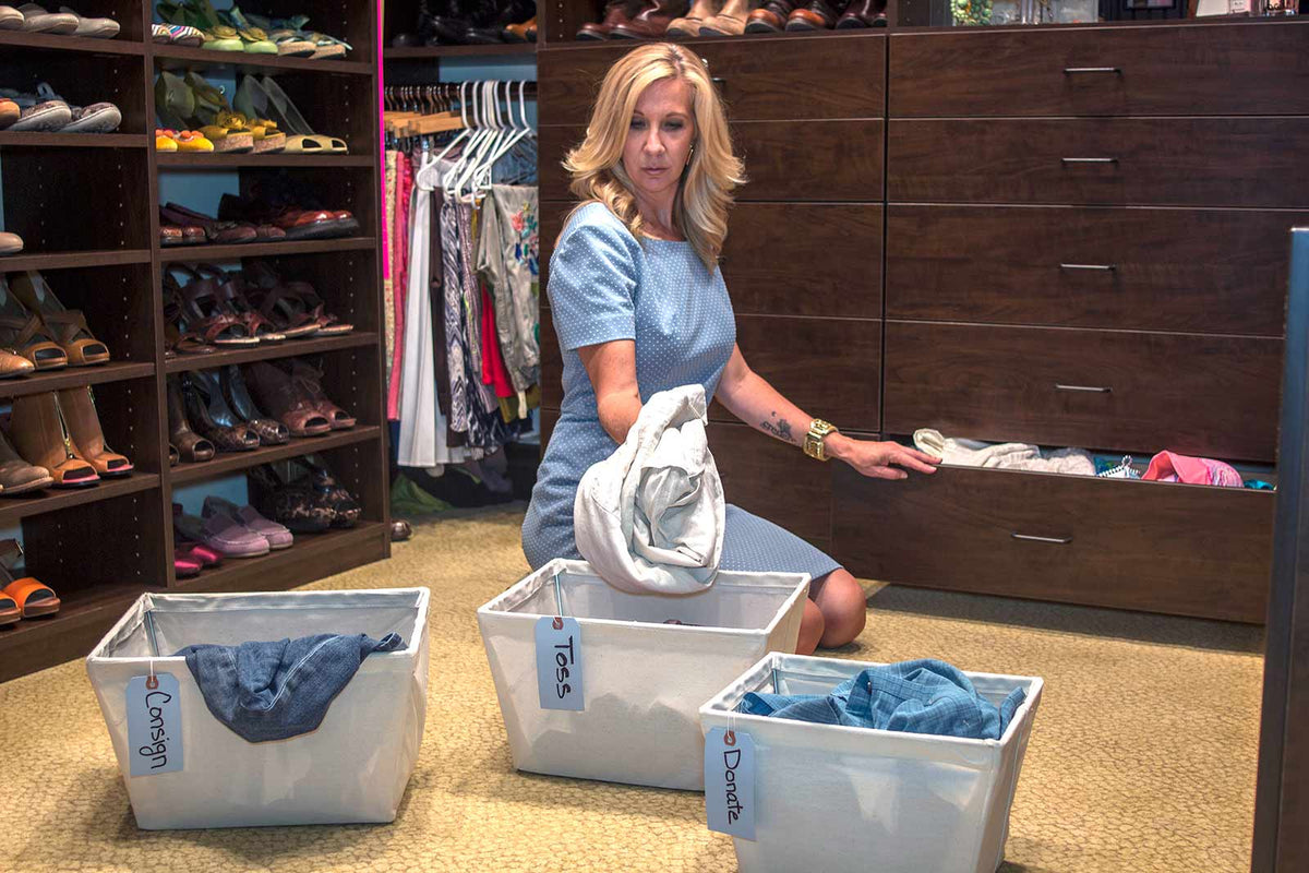 Personal stylist sits in a Solvang CA closet with three bins in front of her labeled toss, donate and consign as part of a closet Audit and Organization process for a client.