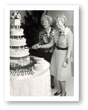 Bill & Salie's daughters, Arlene and Regina, cutting a cake at the 50th anniversary celebration