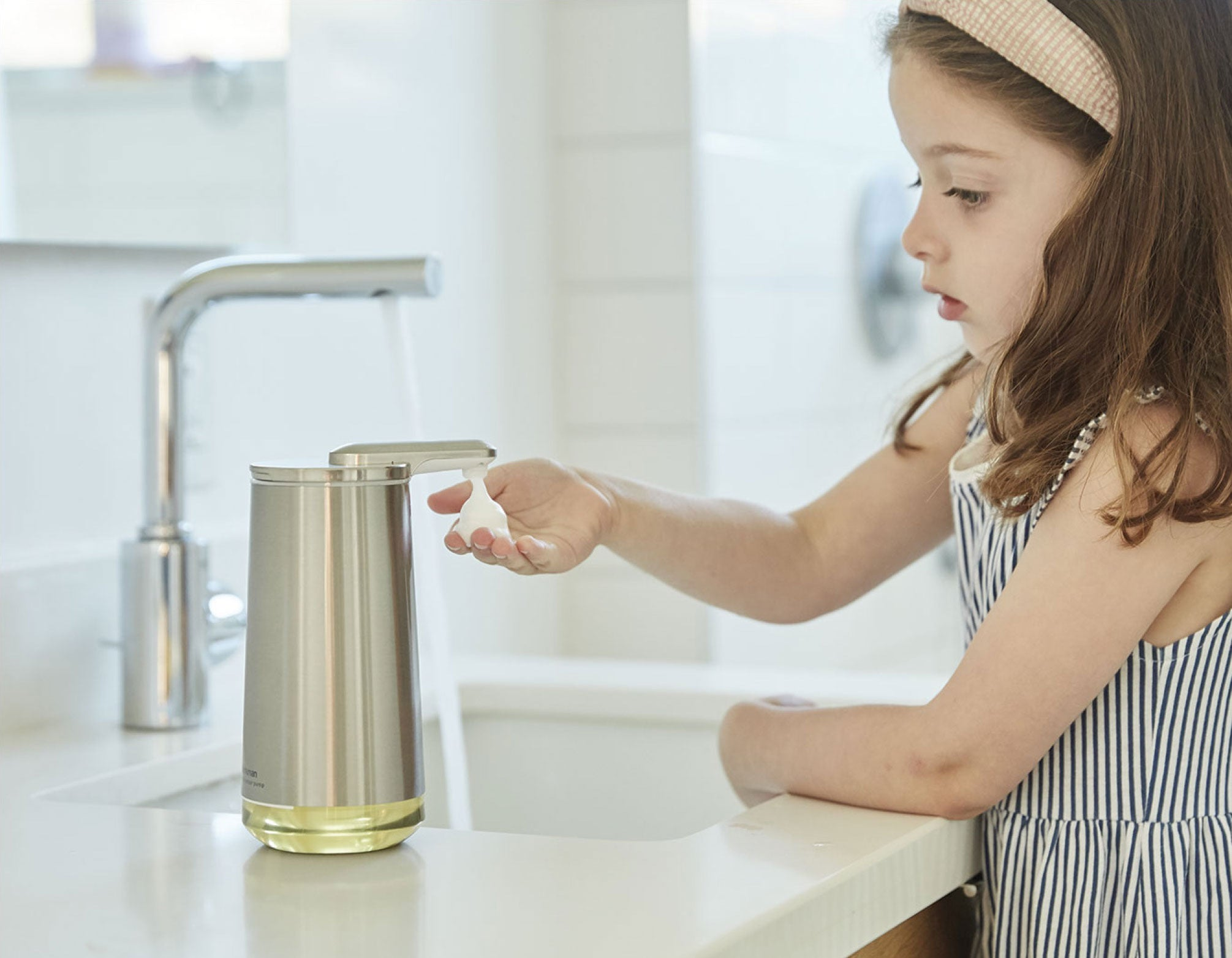 little girl using soap dispenser