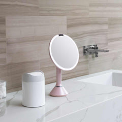 sensor mirror with touch-control brightness - pink finish - lifestyle on counter