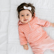 Baby Girl Clothes: little girl laying on bed with long sleeves