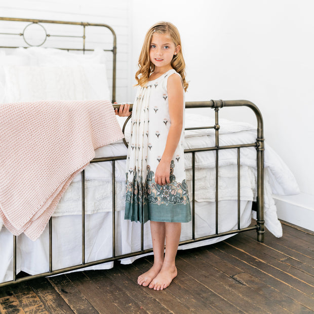 Baby Girl Clothes: girl standing by iron bed