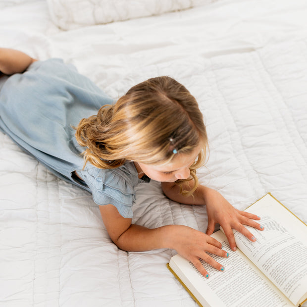 Baby Girl Clothes: reading book on the bed