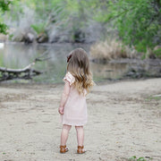Girl stares off into distance in ruffle dress: Baby Girl Clothes