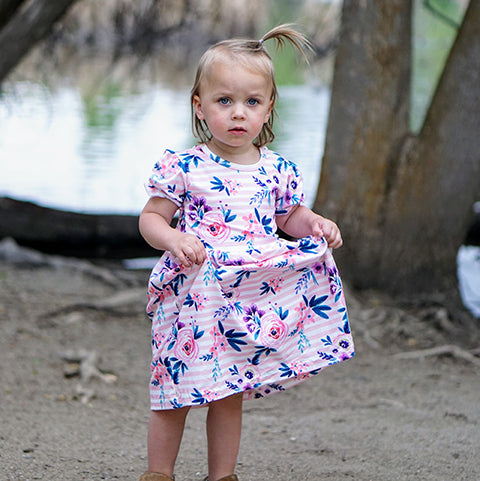 Girl holds flower dress in hand: Baby Girl Clothes