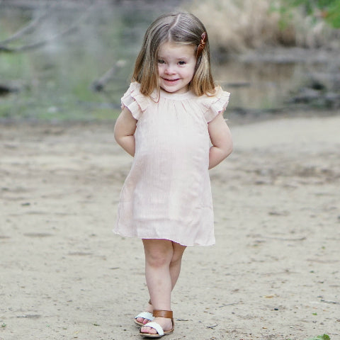 Girl smiles shyly at the camera in Blush Dress: Baby Girl Clothes