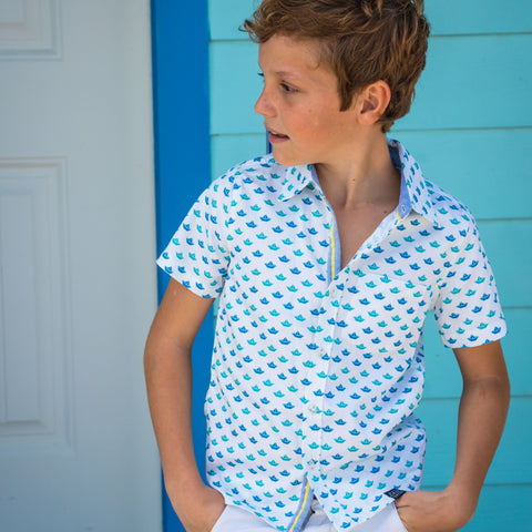 TukTuk Designs short sleeve button up boys shirt in nautical origami sailboat print in blue and green with contrast chambray trim on collar and placket. Available in matching sibling girls dresses.